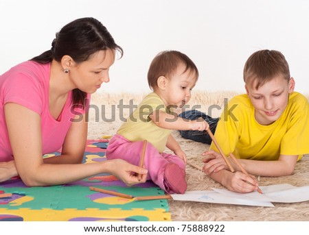 mom and her children drawing on the carpet