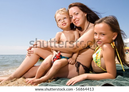 Mom and her children enjoying their vacation at the beach - stock photo