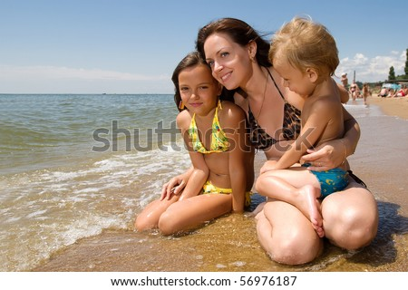 Mom and her children enjoying their vacation at the seaside - stock photo