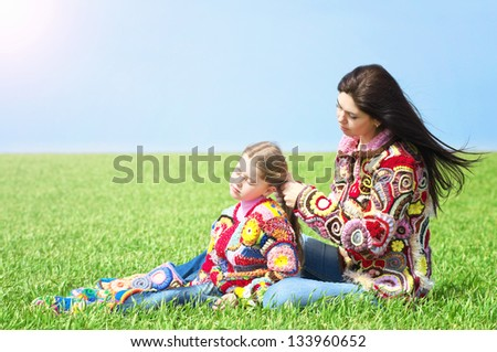 Mom and her daughter in a meadow - stock photo