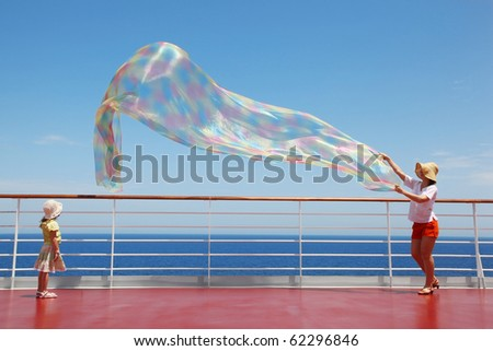 mom and her daughter play with enormous chiffon scarf on deck of yacht - stock photo