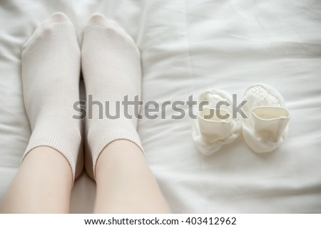 Mom and her future child. Close-up of legs of young pregnant model sitting on the bed near white tiny booties for her baby. Maternity concept - stock photo