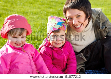 Mom and her lovely toddler girls, outdoors - stock photo