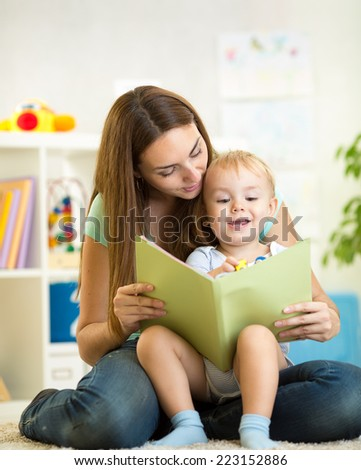 mom and kid boy read a book at home