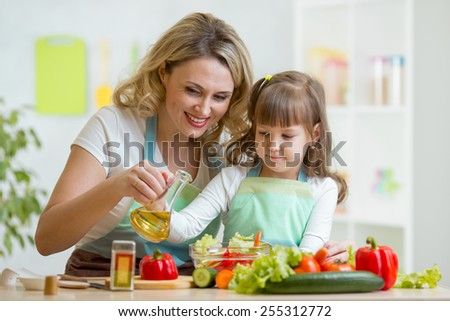 mom and kid girl preparing healthy food at home - stock photo