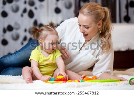 mom and kid toddler play toys at home