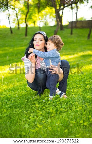 Mom and little boy blowing out dandelion and having fun outside in a sunny day - stock photo