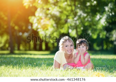 Mom and little daughter lying on front and looking at camera outdoors in the park. Lens flare