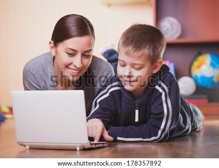mom and son are lying on wood floor with laptop - stock photo