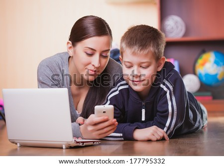 mom and son are lying on wood flooring with laptop - stock photo