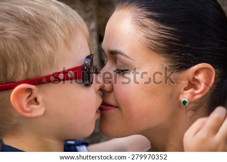 Mom and son. Baby and mom near a stone wall, hugging, kissing, show love. Family values, the concept of family relations.