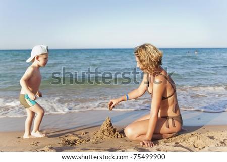 Mom and son building a sand castle on a beach - stock photo