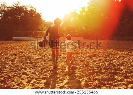 Mom and son having fun by the lake. Warm filter and film effect - stock photo