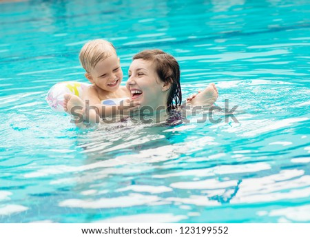 Mom and son having fun playing in the swimming pool - stock photo