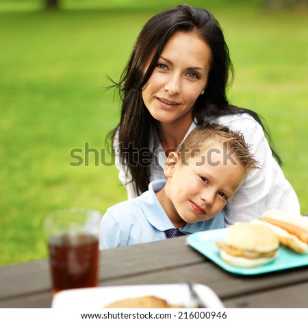 mom and son hugging at picnic table - stock photo