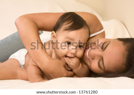 Mom and son lying down on bed and mother embracing the infant baby, who put his hand into mouth - stock photo