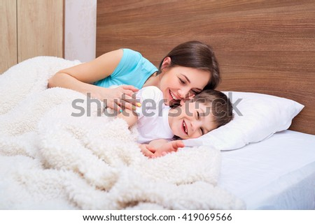 Mom and son playing on the bed. - stock photo