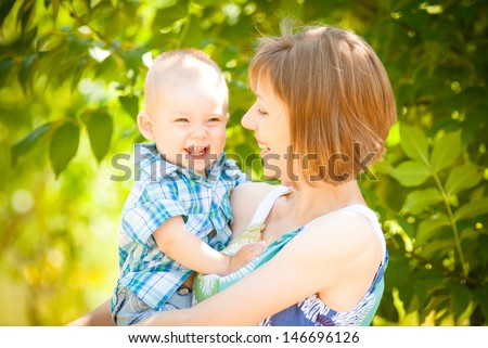 Mom and son playing outdoor together - stock photo