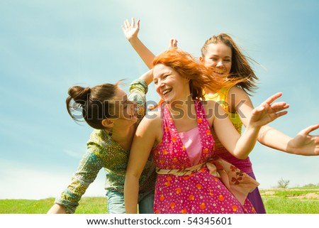 Mom and two Daughter Having Fun under blue sky - stock photo