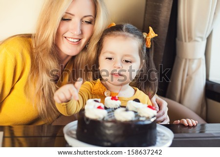 Mom and young daughter celebrating a birthday with cake