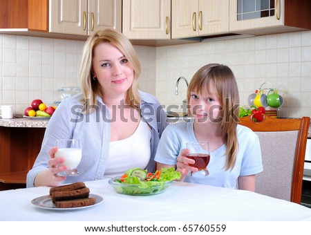 Mom and young daughter eating breakfast together in the kitchen