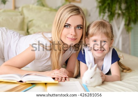 mom blonde with her daughter, lying on bed with books and white rabbit - stock photo