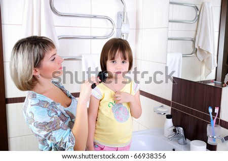 Mom combing hair of his little daughter in the bathroom - stock photo