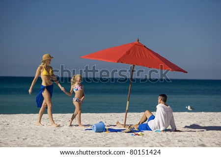 Mom, dad and child enjoying sunny day and white sand.