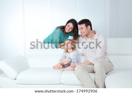 mom dad and daughter sitting on the sofa watching - stock photo
