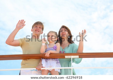 mom dad and daughter wave by hands to ship, which is passed by them - stock photo