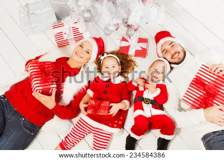 Mom dad and kids with present under Christmas tree - stock photo