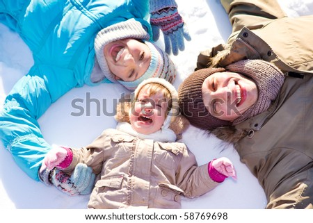 Mom, dad and their daughter lie on snow - stock photo