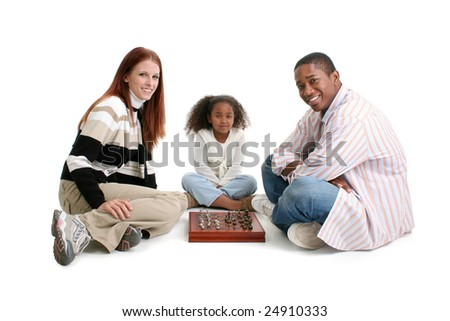 Mom, dad, daughter. Happy interracial family over white background.  Playing Chess. - stock photo