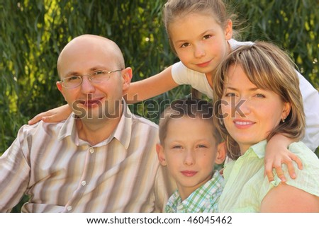 mom, dad, little boy sitting at the grass. little girl is standing behind their. all of them is looking at camera. - stock photo