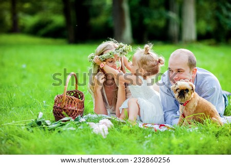 Mom, dad, little girl blonde and dog lie together on the grass and try on a wreath - stock photo