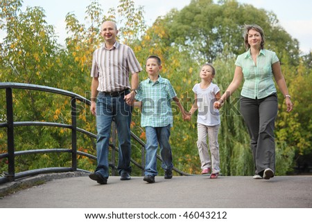 mom, dad, son and daughter is walking on bridge in early fall park. family is handies. - stock photo