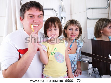 Mom, daughter and father brush their teeth in the bathroom early in the morning. - stock photo