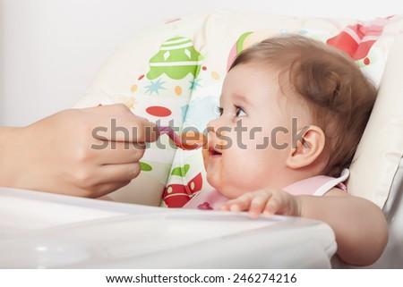 Mom feeding her adorable baby - stock photo