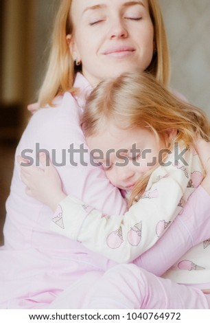 mom gently hugs her daughter on the bed in pink pajamas