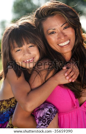 mom giving daughter a piggyback ride - stock photo