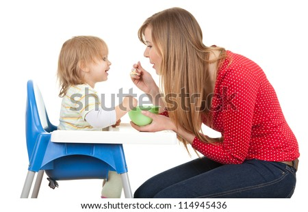 mom giving food to her son on high chair vertical shape, white background - stock photo