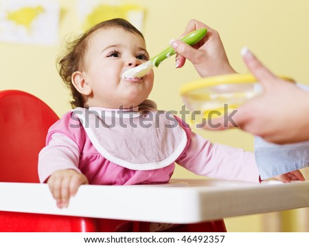 mom giving homogenized food to her daughter on high chair. Horizontal shape - stock photo