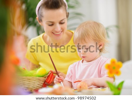 Mom helping baby painting on Easter eggs - stock photo