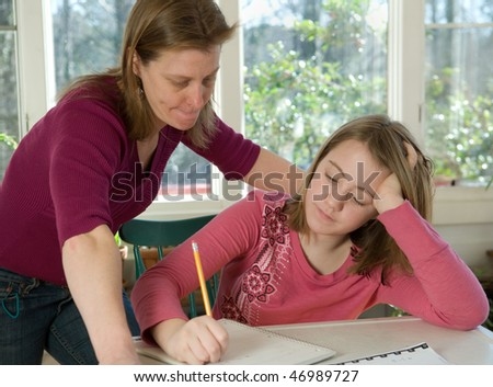 Mom helping daughter with homework - stock photo