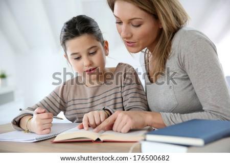 Mom helping kid with homework - stock photo