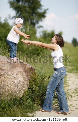 mom helps daughter to go to the ground from large stone