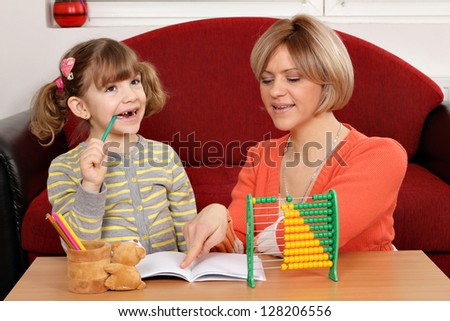 Mom helps daughter to solve homework - stock photo