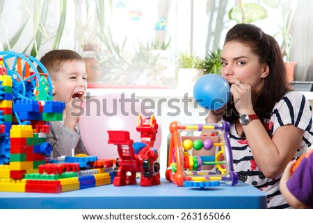 Mom helps son to inflate balloons in home interior - stock photo