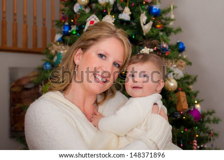 Mom Holding Cute Infant Baby in front of Christmas Tree Wearing Sweater