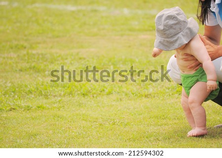 Mom holding little baby trying to walk - stock photo